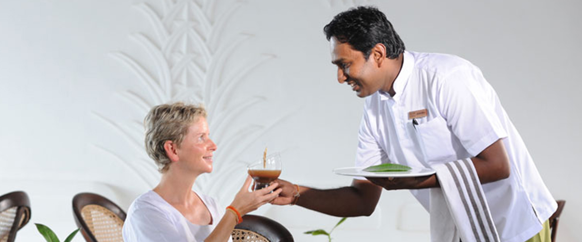 A lady is offered Herbal Juice at Heritance Ayurveda