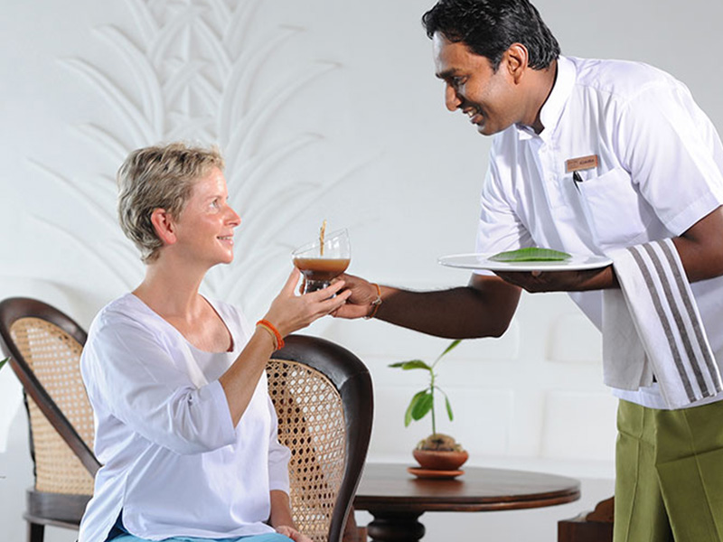 A woman is served a herbal drink at Heritance Ayurveda